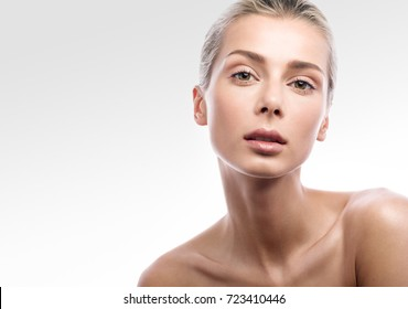 Beauty portrait of female face with natural skin. Beautiful blonde girl with Nude makeup isolated on light gray background. Free space