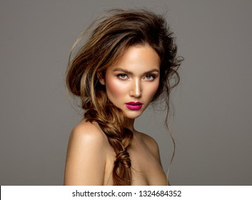 Beauty portrait of female model with braid isolated on gray background