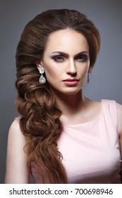 Beauty portrait of a girl with an elegant bridal woven voluminous hair on long dark hair.