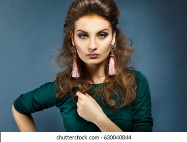 Beauty portrait of a girl on a dark background.Long earrings. Evening make-up .