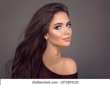 Beauty portrait of gorgeous aesthetic woman with natural makeup and matte lipstick. Pretty brunette model with long shiny wavy hair style isolated on studio gray background.