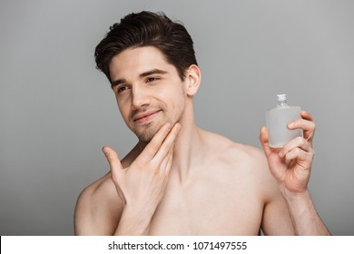 Beauty portrait of half naked handsome young man using aftershave lotion isolated over gray background
