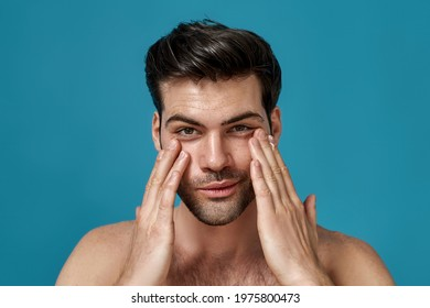 Beauty portrait of handsome man looking at camera with a smile while applying moisturizing cream on his face isolated over blue background. Skincare routine concept. Horizontal shot