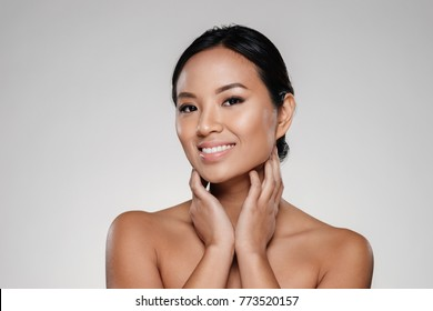 Beauty portrait of a happy half naked asian woman looking at camera isolated over gray background
