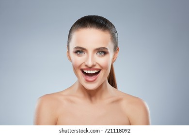 Beauty portrait of happy smiling girl looking at camera. Head and shoulders of cheerful beautiful woman with wide smile. Natural make up, studio, true emotions