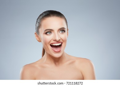 Beauty portrait of happy smiling girl looking up. Head and shoulders of cheerful beautiful woman with wide smile. Natural make up, studio, true emotions