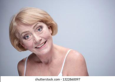 beauty portrait of happy smiling mature woman face skin teeth head and sholders isolated on blue background looking at camera