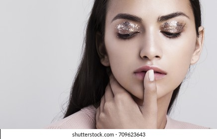 A beauty portrait of an indian model with glitter makeup touching her lips.