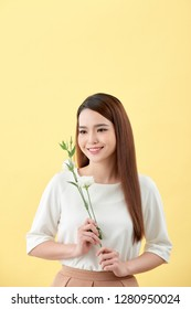 Beauty portrait of lady 20s holding white lisianthus flowers over yellow background