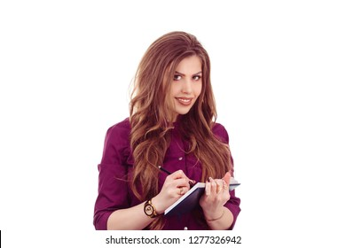 Beauty portrait of Latin American woman with notebook pen in hands taking notes isolated on white background. Eyebrows micropigmentation nurse specialist in formal wear looking at camera happy writing