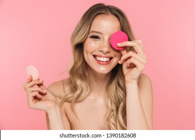Beauty portrait of a lovely young woman with long blonde hair standing isolated over pink background, using makeup sponge