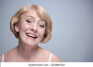beauty portrait of mature caucasian blond woman face skin teeth happy cheerful toothy smile isolated on blue background