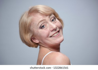 beauty portrait of mature caucasian woman blond face skin teeth thoothy smile isolated on blue background