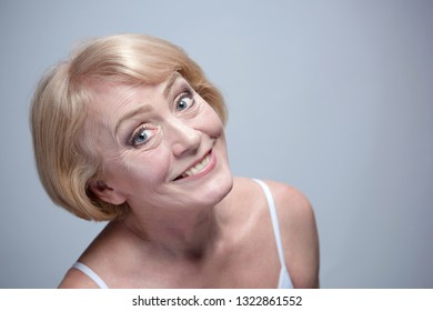 beauty portrait of mature woman blond face skin head and sholders smiling cheerful isolated on blue background