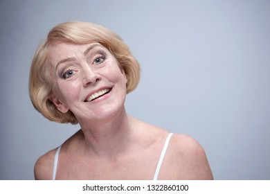beauty portrait of mature woman face skin smile smiling happy teeth toothe smiling head and sholders isolated on blue background