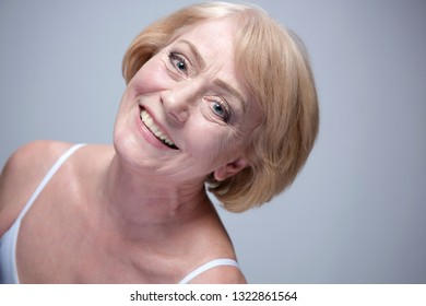 beauty portrait of mature woman face skin teeth happy toorhy smile cheerful head and sholders isolated on blue background