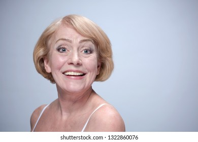 beauty portrait of mature woman happy toothy smiling face skin teeth head and sholders isolated on blue background
