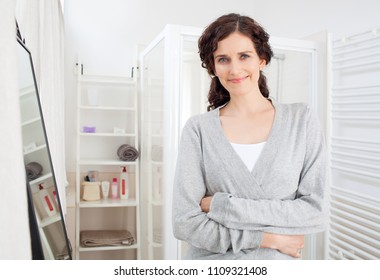 Beauty portrait of middle age woman grooming in white space bathroom wearing robe, smiling serene looking at camera, home interior. Healthy mature female skin care, wellness and well being lifestyle.
