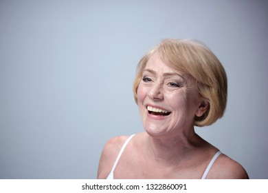 beauty portrait og mature caucasian happy laughing woman face skin teeth blond head and sholders isolated on blue background