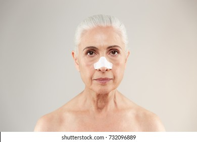 Beauty portrait of an old half naked lady with clear-up patches on her nose to remove blackhead isolated over white background