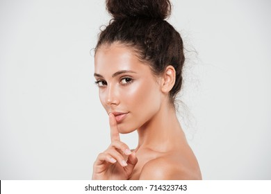 Beauty portrait of a pretty smiling woman with healthy skin showing silence gesture with finger over her lips isolated over white background