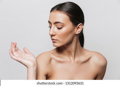 Beauty portrait of a pretty young topless woman standing isolated over white background, posing