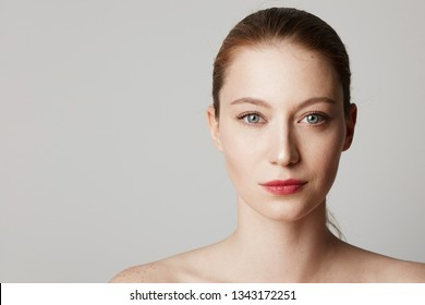 Beauty portrait of a pretty young topless redhead girl with freckles isolated over white background. Cosmetology and Advertisement.