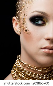 Beauty portrait of pretty young woman with golden leafs on the face and professional make up