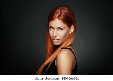 Beauty portrait of a red-haired woman with blue eyes in a studio on a dark background