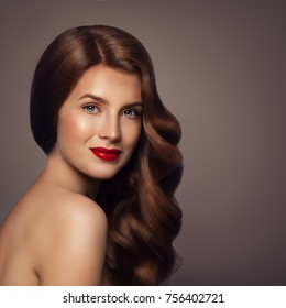 Beauty Portrait of Redhead Woman with Healthy Wavy Hair. Elegant Lady with Perfect Hairstyle