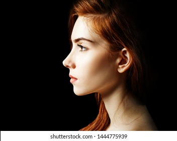 Beauty portrait of redhead woman. Over black background.