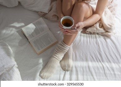 Beauty Portrait Relaxed Woman in the Morning   and Drinks Coffee in Bed. Attractive Woman Reading  Book and  Bed . Caucasian young woman    Relaxed  in Bed and Reads a Book