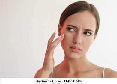 schoonheid portret van trieste vrouw het aanraken van haar huid op witte achtergrond
