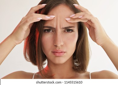 beauty portrait of sad woman touching her skin on white background