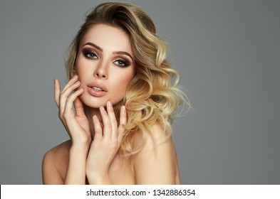 Beauty portrait of seductive blond woman touching her face isolated on gray background