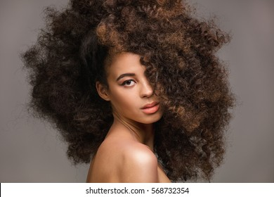 Beauty portrait of sensual african american woman with long curly hair , looking at camera.