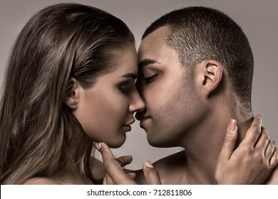 Beauty portrait of sensual beautiful kissing couple. Caucasian woman with glamour makeup posing with handsome african american man.
