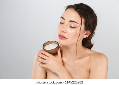 Beauty portrait of a sensual young topless woman with make-up holding glass of sea salt isolated over gray background