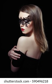 Beauty portrait of sexy mysterious woman in lace mask on a black background.