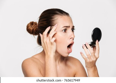 Beauty portrait of a shocked young half naked woman examining her face while looking at the mirror isolated over white background