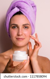 Beauty portrait of a smiling beautiful half naked woman holding container with a face cream and pink towel.
