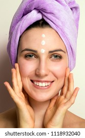 Beauty portrait of a smiling beautiful half naked woman on beauty center touching face wearing pink towel.