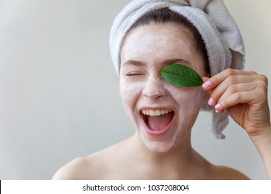 Beauty portrait of a smiling brunette woman in a towel on the head with white nourishing mask or creme on face and green leaf in hand on white background isolated. Skincare cleansing eco organic