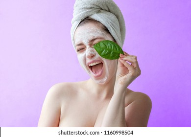 Beauty portrait of a smiling brunette woman in a towel on the head with white nourishing mask or creme on face and green leaf in hand on purple background isolated. Skincare cleansing eco organic - Shutterstock ID 1160998504