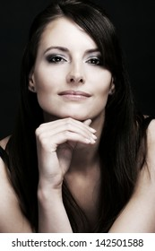 Beauty portrait of a smiling caucasian woman with long brown hairs, intense look in her eyes and resting her chin in the hand, looking at the camera on a black background