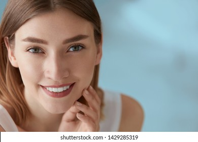 Beauty portrait of smiling woman with white teeth smile. Beautiful happy girl with fresh skin, natural face makeup indoors closeup