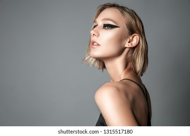 Beauty portrait of stylish blond woman with creative professional make up over grey background. Copy space.