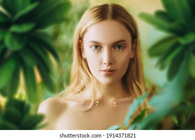 Beauty portrait of a tender blonde girl with fresh shining makeup among tropical greenery. Spa, skincare and cosmetics. Pearl jewelry.