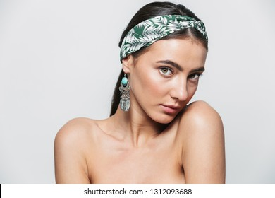 Beauty portrait of a topless young beautiful woman wearing headband and earrings standing isolated over white background