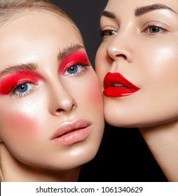 Beauty portrait of two women with red glamour make up. Red lips and red eyeshadows.